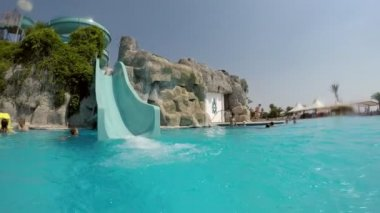 Kemer, Turkey - July 18, 2017:A jolly view of a young man moving down from a high slide in a Turkish aquapark in summer. The blue waters look good.