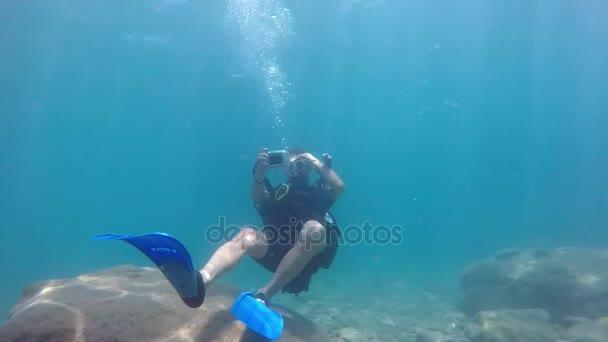 kemer, Türkei - 18. Juli 2017: Ein Taucher hält eine kleine Kamera in der Hand und filmt das Schwimmen in der Nähe des steinigen Mittelmeerbodens im Sommer in Zeitlupe.