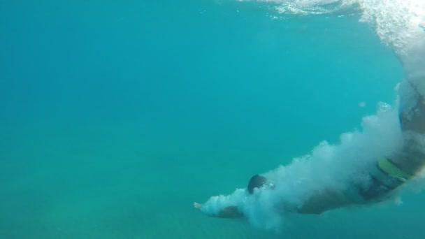 Una vista allegra di un giovane immergendosi nel mare Mediterraneo in una giornata di sole in estate al rallentatore. Egli provoca un sacco di bolle daria