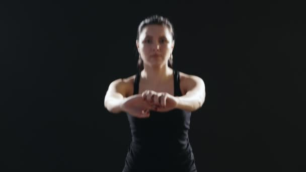 Slim woman with a pony-tail does sit-ups on a yoga mat in a black studio                                  A wonderful view of a fitness instructor who does sit-ups being dressed in a black singlet and pants. She does it energetically in a black gym.