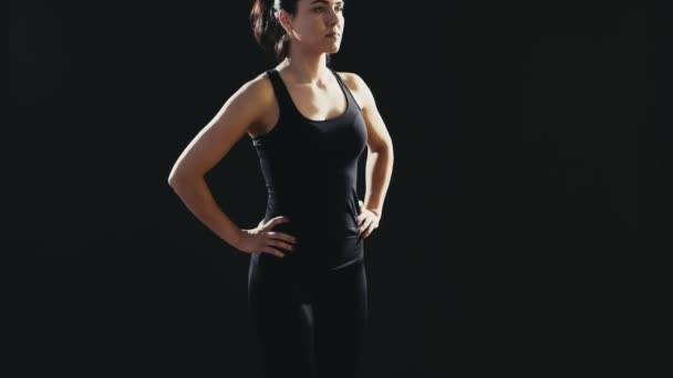 Sportive woman with a pony-tail does back lunges on a mat in a black studio                          An encouraging view of a fitness instructor who does back lunges dressed in a black sportive suit. She does it professionaly in a black gym.