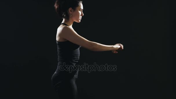 Slender woman with a pony-tail does sit-ups on a yoga mat in a black studio                           An inspiring view of a fitness instructor who does sit-ups being dressed in a black singlet and pants. She does it energetically in a black gym.