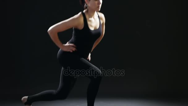 Sportive woman with a pony-tail does back lunges on a yoga mat in a black studio                         An educative view of a fitness instructor who does back lunges being dressed in a black sportive suit. She does it professionaly in a black gym.