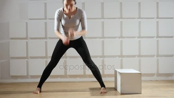 Sportive woman stands and keeps her legs wide to bend forward energetically                               An educative view of an athletic woman in a tshirt and black pants who stands and keeps her legs wide while bending forwardd and her legs.