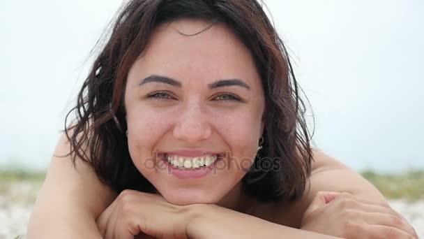 Mosolygó nő fekszik, a Fekete-tenger partjától és nevet boldogan slo-Mo nyáron egy vidám nézet hullámos hajjal, fiatal barna nő, aki fekszik a Fekete-tenger homokos, a mosoly és a nevetés, élvezi az életét, a lassú mozgás.
