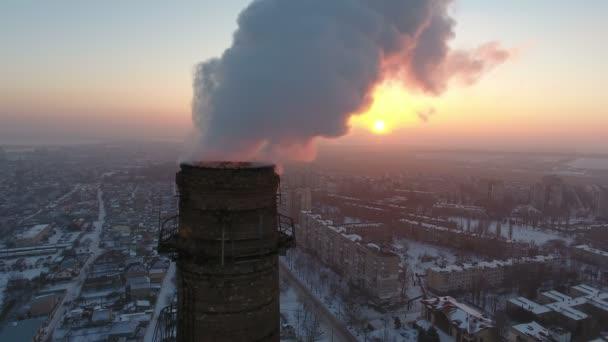 Légi Vértes lövés, egy nagy ipari torony fehér füst, napnyugtakor a téli A madár szem Vértes lyukat egy hatalmas tégla-torony, a flux sűrű a szmog a téli naplemente szemcsésedik-ból egy közeli repülő drone