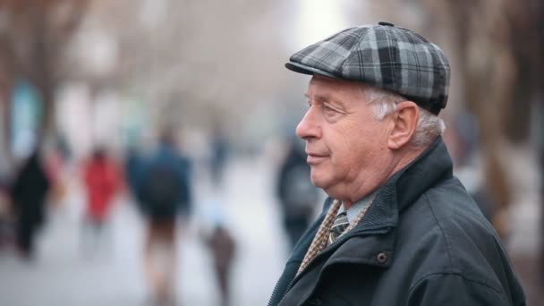 An old gentleman in a woollen flat cap stands in profile in an alley in  autumn. A profile view of a senior man dressed in a black zipup coat and a  woollen ... e0e3369b0ee