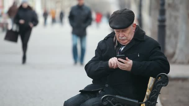 6d0a248889e A wise old man sits on a bench and dials his mobile in a park alley in  autumn A wonderful view of a wise senior man in a black jacket and a ...