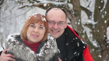 Happy husband hugs his blond wife in a fur coat under falling snow in a park.                           A romantic view of a cheery bald husband in glasses embracing his happy blond wife in a snowy park in winter. They smile happily under heavy snow.