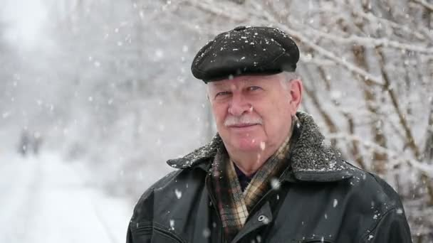 62457aae87d A happy old man stands under heavy snowflakes in a splendid park in winter  An amazing view of a senior man with white mustashe in a flat cap.