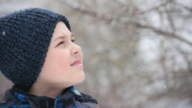 A funny boy looks up in a park. The falling snowflakes look gorgeous in winter                                An amazing profile of a curious nine-year-old boy in a black knitted hat. He looks up at white and heavy snowflakes in a park in winter