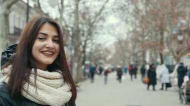 A happy girl stands in a park alley and smiles sincerely in winter in slo-mo                                     A wonderful view of a smiling girl with long loose hair. She is dressed in a black parka and white scarf.She stands in a park alley.