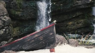 A small waterfall falls from big rocks in a pond with a boat standing nearby                                     An amazing view of a forest waterfall with sparkling splashes falling from rocks in a narrow pond. A wooden boat stands near in autumn.