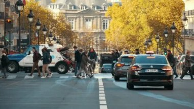 Paris, France - November 3, 2017:    A heartwarming view of elegant pedestrians crossing the picturesque street in Paris in autumn. A female cyclist rides across them in slow motion..