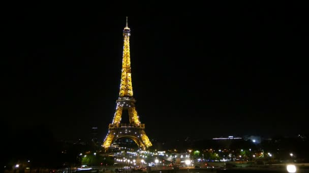 Paris, France - November 3, 2017:An effective time lapse view of the Eiffel Tower in Paris. The cars rush under its pillars. It has sparkling yellow backlighting at night