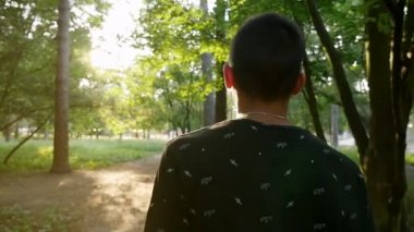 Sportive young man goes along a footpath to a sunrise in a park in slo-mo                                   An amazing view of a sparkling sunrise and a young handsome man going towards the sun through a splendid park in summer in slow motion