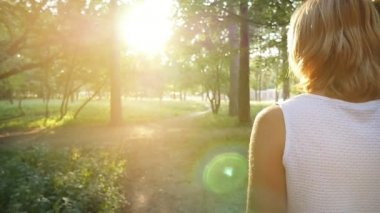 A slender blond woman goes along a lane towards a splendid sunrise in a park                           An amazing view of a beautiful woman in a sleeveless white dress moving to a shining sun at a picturesque sunrise in a park in summer in slo-mo
