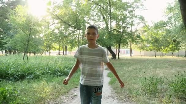 A small boy goes along a lane in a green park at sunset in slow motion                                     A gorgeous view of a sportive nine year boy walking ahead in a magic looking park in summer in slow motion. He is in a striped tshirt and jeans