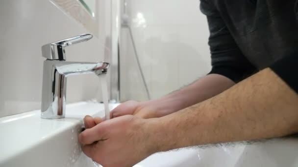 Muž středního věku umyje obličej pod kohoutkem z nerezové oceli v pomalém pohybu původní closeup z nerezové oceli fauced řízení zahájeného muž středního věku v koupelně. Myje obličej pod Streemové v slo-mo