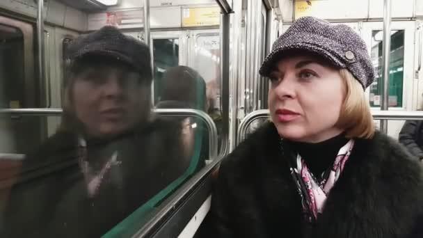 Glamour parisien blonďatá dáma jezdí ve voze metra a vypadá v okně Detailní stylový blonďatá žena oblečená v černý kožich, hedvábný šátek a elegantní klobouk sedí v jedoucího vozu metra v Paříži na podzim