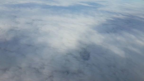 Letecký snímek z tryskové letadlo cestující letící nad nadýchané šedé mraky A ohromující výhled z okna Letadlo jet létání nad divoké a drsné šedá a bílá oblaka s modré tečky na ošklivý den v létě