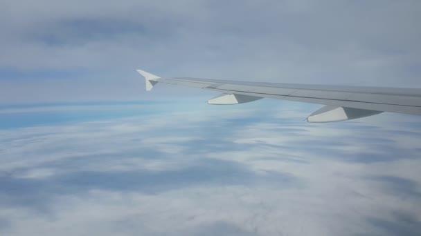 Luftaufnahme aus einem Passagierflugzeug, das über weißen und grauen Wolken fliegt, ein traumhafter Blick aus dem Fenster eines Düsenflugzeugs, das an einem fiesen Sommertag über rätselhaften und wuchernden grauen und weißen Wolken fliegt.