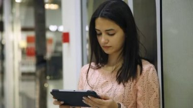 Slender girl stands and looks attentively at her tablet in a modern supermarket                                Portrait of a stylish young woman touching the screen of her tablet and analyzing the prices while standing in a modern supermarket