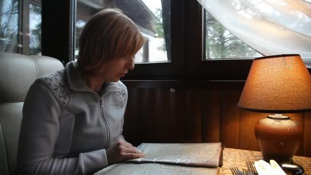 Elegantní blondýna žena vypadá prostřednictvím menu v pařížské kavárně na podzim portrét elegantní blondýnka sedí a na podzim při pohledu přes menu v útulné kavárně v Paříži. Cítí se šťastná a uvolněná