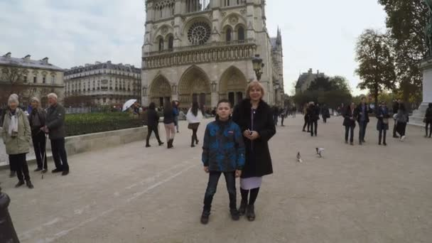 Paris, France - November 9, 2017:    A dolly in shot of a smiling blond mother and her boy near Notre Dame de Paris with ancient domes, columns, archs, decor in autumn in slo-mo