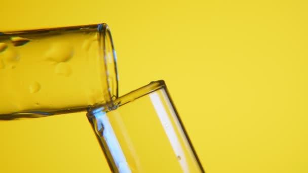 Lucidní kapalina se přelije z jedné zkumavky do druhé ve vědecké laboratoři makro snímek dvou laboratoří trubek s bílými čarami. Tekutina se přelije z jedné mokré zkumavky do druhého v pozadí žluté
