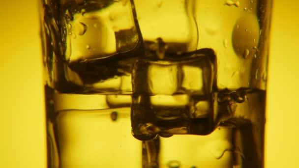 Zlaté ledových kostek skla a vody v ní se svítícím bubliny bohémský makro záběr crystaline skla plné kostek ledu na žlutém pozadí. Proud sladké vody se nalévá do skla