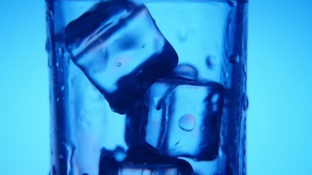 bläuliche Eiswürfel in einem Glas und Wasser, das mit leuchtenden Blasen einströmt, eine kunstvolle Makroaufnahme eines kristallklaren Glases voller Eiswürfel vor blauem Hintergrund. ein Strom von frischem Wasser ergießt sich ins Glas