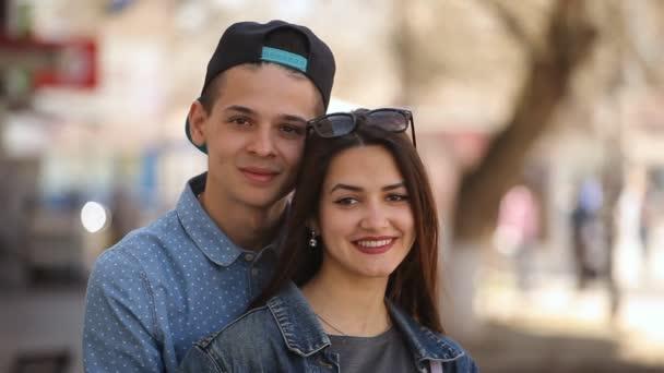 Krásný mladý pár stojí v uličce vzdušné a šťastně usmívat na jaře portrét nabídka mladé ženy s krásnou dlouhé rozpuštěné vlasy a její mladý přítel romanticky usmívá a stál v uličce vzdušné na jaře