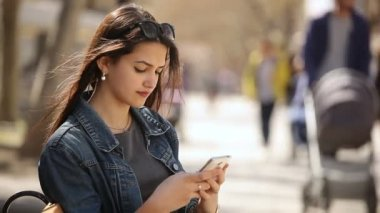 Elegant woman touches the screen of her smartphone sitting on an alley bench in spring                         Profile of a stylish young woman with sunglasses using her mobile and sitting on a bench in an airy alley on a sunny day in spring