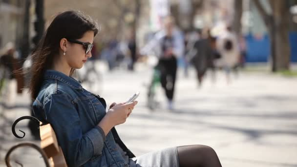 Successful woman surfing the net on her smartphone sitting on an alley bench                         Profile of an attractive young woman with sunglasses browsing the net on her mobile and sitting on a bench in a nice alley on a sunny day in spring