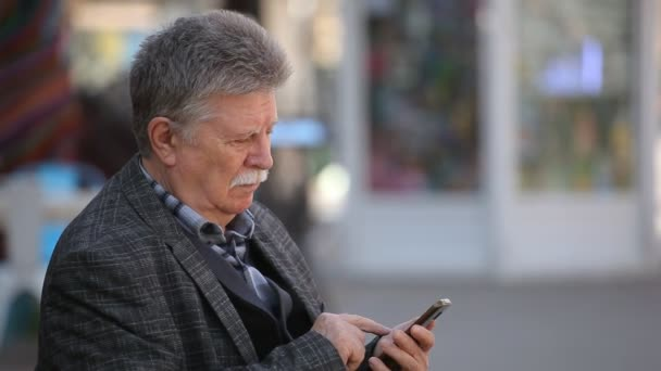 66f21ff220e A smart old man logs on the web on his mobile in a city street in spring  Bokeh portrait of a confident senior man with a mustache surfing the net on  his ...
