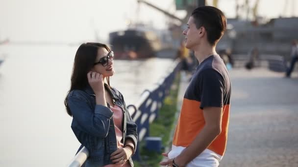 Young man chats with a nice girl in sunglasses on the Dnipro quay in spring                                Bokeh shot of a romantic young couple talking and smiling at the Dnipro in spring. The girl is in sunglasses. A yacht is moving in the backdrop