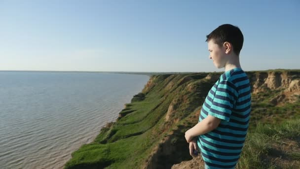 Optimistic boy observes blue waters of the Black Sea in summer in slo-mo                                A  dreamlike profile of a small boy in a striped t-shirt standing at the Black Sea and looking at the blue waves on a sunny day in slow motion