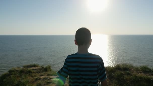 Small boy goes to the Black Sea at a splendid sunset in summer in slow motion                           An exciting back view of a nine-year old boy walking to the Black Sea coast and looking at a splendid sunset with a sparkling sun path in slo-mo