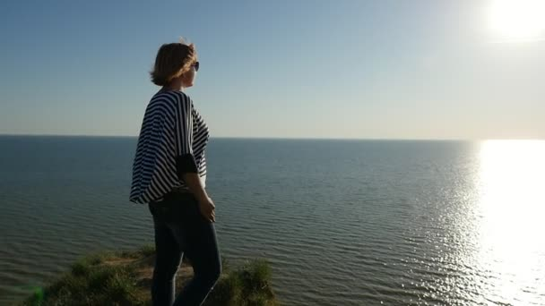 Amazing blond woman stands on the Black Sea coast at sunset in slow motion                              Profile of a stylish woman in a waving striped blouse and sunglasses standing at the Black Sea  at a splendid sunset with a sun path in slo-mo