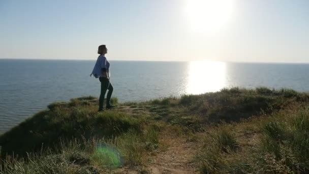 Blond woman stands on the Black Sea coast at a sparkling sun path in slo-mo                                An amazing view of a stylish blond woman standing on the Black Sea shore and looking at a golden sun path looking like a fire pillar in slo-mo