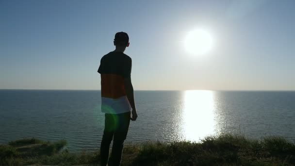 Tough young man stands on the Black Sea shore at golden sunset in slo-mo                           Back view of a smart man in a striped T-shirt,  cap, and pants standing at the Black Sea and looking cheerfully at the golden path at sunset in slo-mo