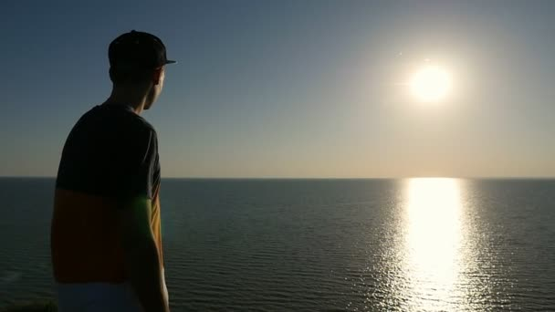 Cool young man stands on the Black Sea shore at shining sunset in slo-mo                           Back view of a cheerful man in a striped T-shirt,  cap, and pants standing at the Black Sea and looking at the golden sun path at sunset in slo-mo