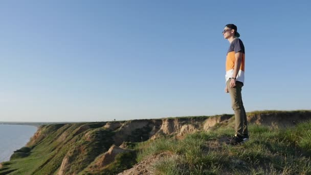 Excited young man stands on the hilly Black Sea coast in summer in slo-mo                           Profile of a brisk man in a baseball cap, sunglasses and a T-shirt standing on the Black Sea coast and enjoying the seascape in summer in slow motion
