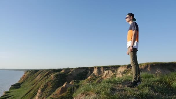 Enthusiastic young man stands on the hilly Black Sea coast in summer in slo-mo                           Profile of a vivid man in a baseball cap, sunglasses and a T-shirt standing on the Black Sea coast and observing the sea in summer in slow motion