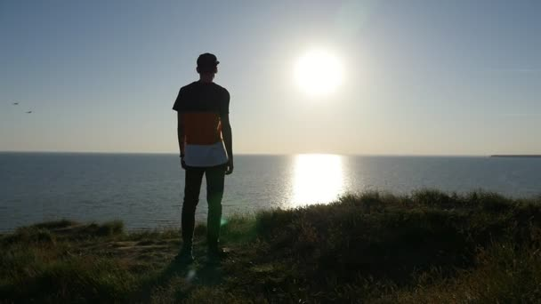 Romantic young man stands on the Black Sea coast at shining sunset in slo-mo                           Back view of a sportive man in a baseball cap and a T-shirt standing on the Black Sea shore and enjoying the golden sun path at sunset in slo-mo