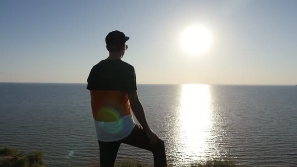 Snappy young man stands on the Black Sea shore at golden sunset in slo-mo                           Profile of a sportive man with a crew haircut in cap and a T-shirt standing on the Black Sea shore and keeping one leg bent at fine sunset in slo-mo