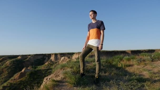 Stylish young man stands on the Black Sea coast at looks forward in slo-mo                           Profile of a cheery young man with a crew haircut in a T-shirt standing on the Black sea coast and enjoying the picturesque view in summer in slo-mo
