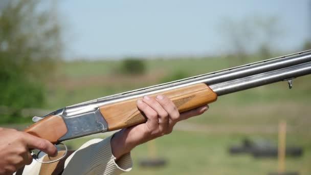 Sportsman gyakorló skeet számos puskáját a slo-mo profil egy vadász, emelése a fölött és alatt dupla hordó shortgun, és a forgatás a slo-mo nyáron. A puska ütődésektől a visszarúgás, egy napsütéses napon