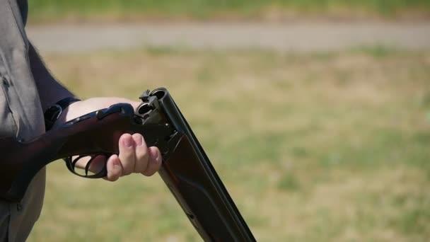 Mann macht eine Pause-Aktion, lädt seine über- und Shortgun im Sommer in Slo-Mo Nahaufnahme eines Mannes eine Patrone in einer Beckenendlage sein doppeltes Federhaus Gewehr und mit einem Sicherheitsriegel auf einer Palette im Sommer in Zeitlupe